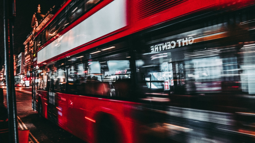 Red bus driving through a street at night