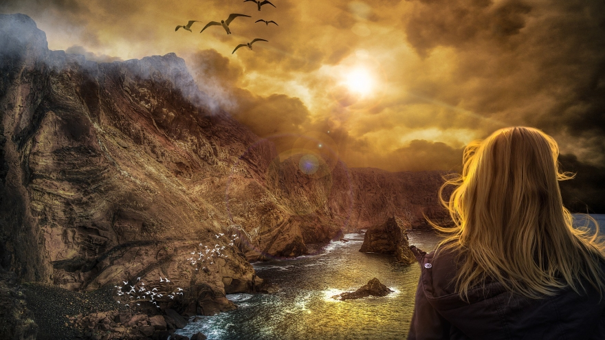 Blond woman overlooking a cliff and the ocean with seagulls flying in the air